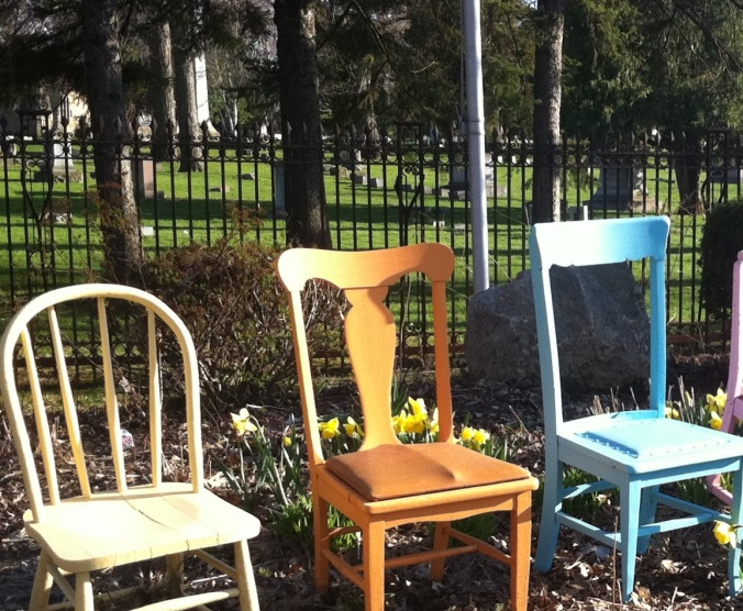 Pastel colored chairs in front of a cemetery